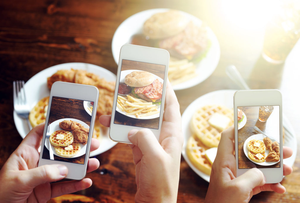friends using smartphones to take photos of food with instagram style filter at restaurant
