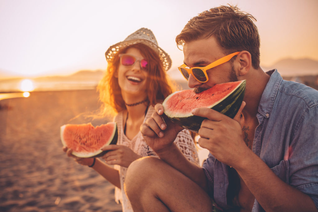 Hipster couple sitting on the beach and eating watermelon. Wearing casual summer clothing, hat and sunglasses. Enjoying in sunset by the sea.