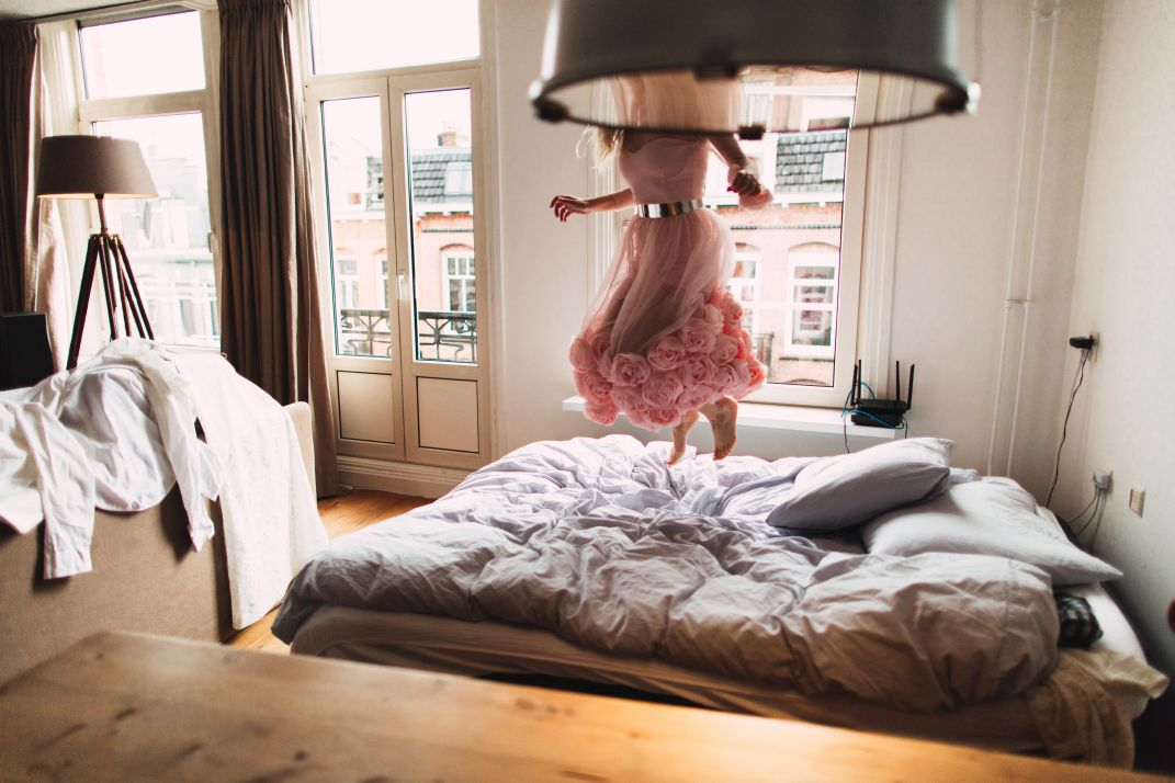 Portrait of a beautiful bride, jumping on the bed of excitement